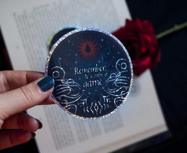 """Se sostiene en una mano la Sticker Caraval. Esta es de forma redonda, contiene tonos en azul eléctrico, detalles en glitter plateado y una frase en inglés que pone """"Remember, It's only a game"""""""