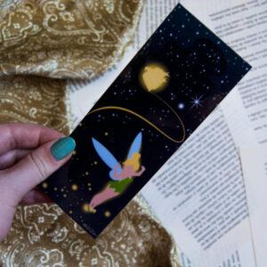 Se sostiene sobre una mano el Marcapáginas Campanilla. Este contiene un fondo oscuro con detalles en dorado y plateado simulando estrellas. Campanilla aparece en la parte inferior derecha