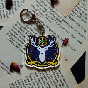 Se expone el llavero Trono de Cristal. Este contiene un ciervo en color blanco, sobre un fondo azul eléctrico. Además, contiene tonos dorados rodeándolo
